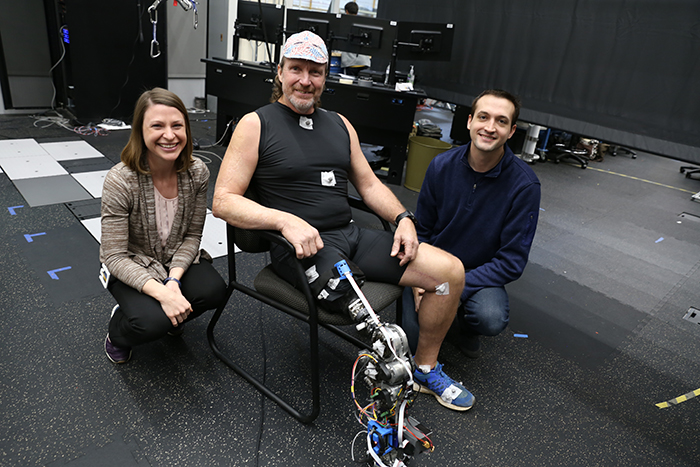 Clinician Kinsey Herrin and Aaron Young with a patient wearing the robotic lower limb