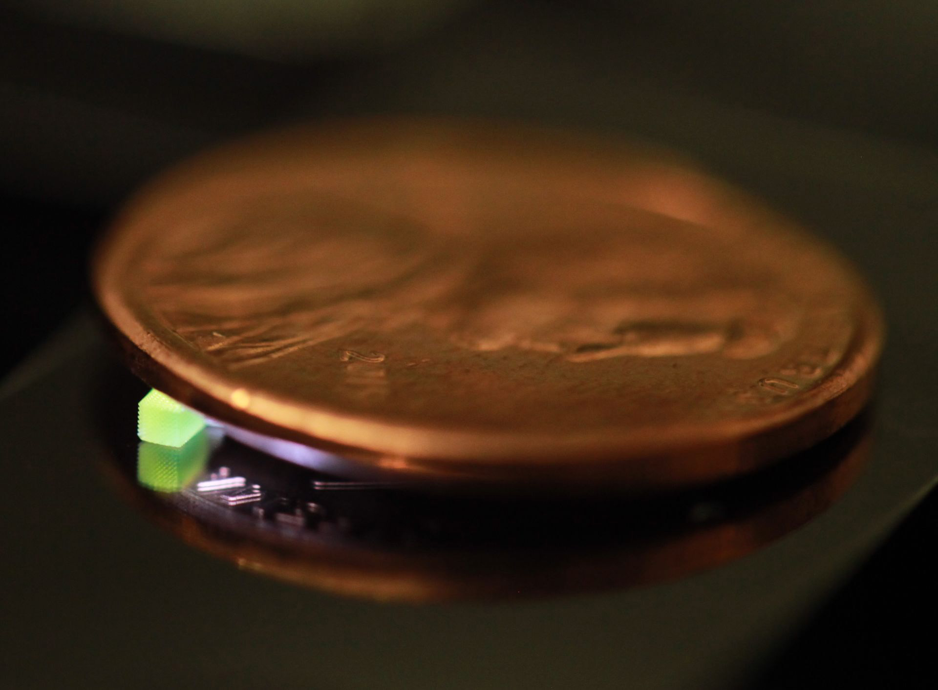 A millimeter-scale structure with submicron features is supported on a U.S. penny on top of a reflective surface. (Credit: Vu Nguyen and Sourabh Saha)