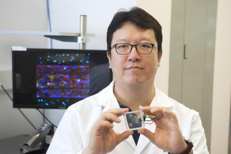 YongTae Kim holds up microfluidic chip