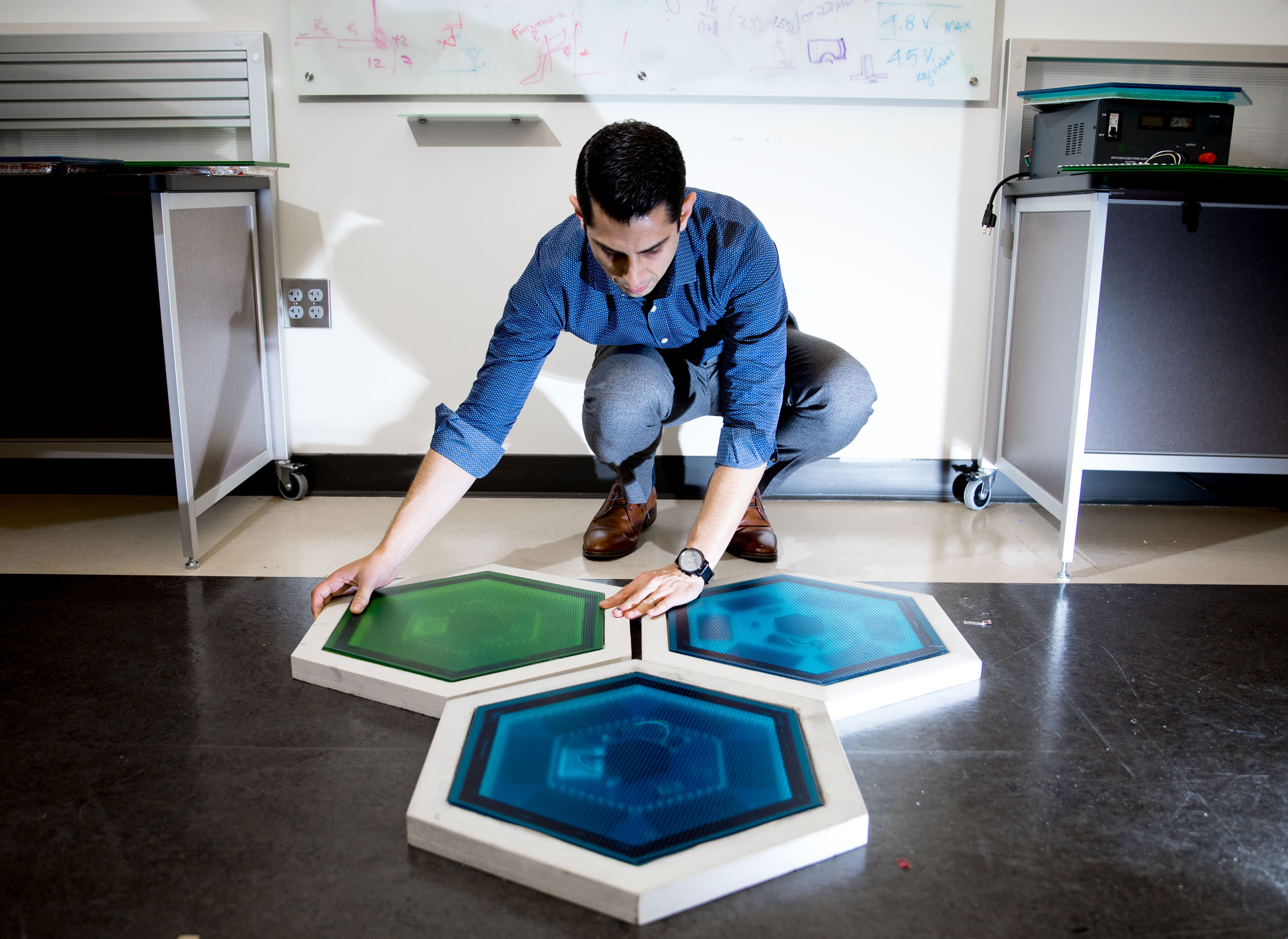 Ilan Stern, a GTRI senior research scientist, shows piezoelectric tiles that will be used to create a lighted outdoor footpath at the NASA Kennedy Space Center's Visitor Complex at Cape Canaveral, Florida. He's holding the electronic components used in th