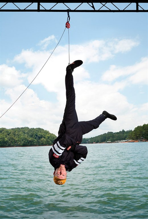 ME alumnus Ian Eyre, stuntman, hanging upside down from structure over water